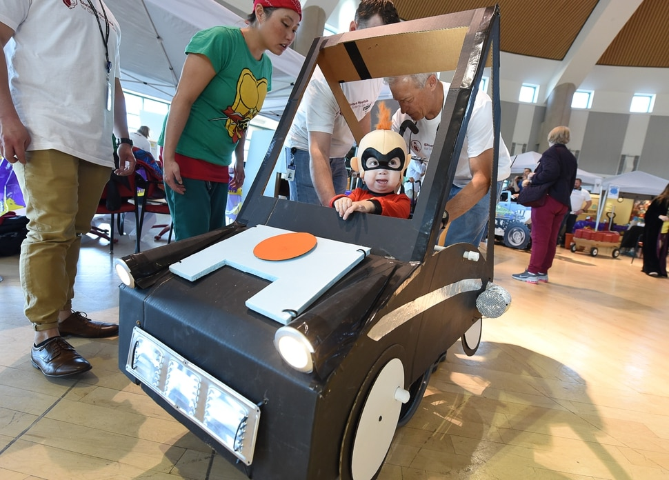 (Francisco Kjolseth | The Salt Lake Tribune) Cooper Baskett, 3, assumes the role of Jack-Jack from the movie The Incredibles as a small army of volunteers and staff at Shriners Hospital for Children in Salt Lake put the finishing touches on his Incredimobile and those of another 27 patients in wheelchairs for Halloween, Wednesday, Oct. 17, 2018. Cooper, who has skeletal dysplasia, relished the attention, frequently flashing some of his character's signature moves. This is something he gets to have all his own, exclaimed his mother, Tonya Baskett.