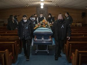 (Victor J. Blue | The New York Times) Pall bearers with the coffin of Jesse Taken Alive, a Lakota member of the Standing Rock Tribe who died of COVID-19, at Kesling Funeral Home in Mobridge, S.D., on Dec. 26, 2020. The coronavirus has killed American Indians at especially high rates, robbing tribes of precious bonds and repositories of language and tradition.