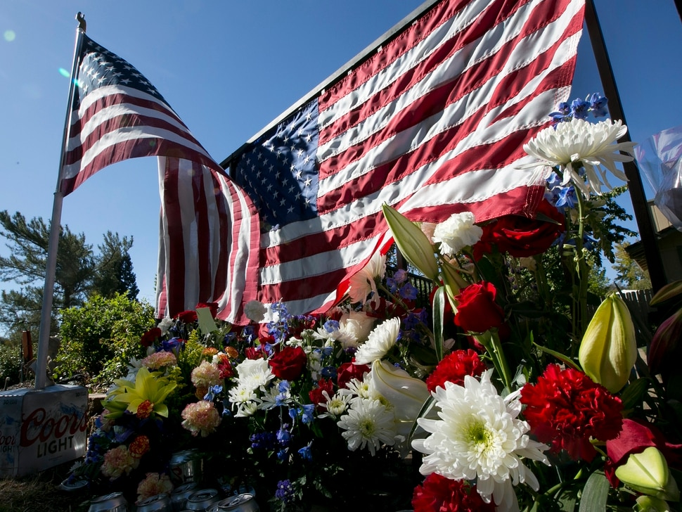 Flags and flowers make up a memorial on the backyard fence of Las Vegas shooting victim Kurt Von Tillow, Wednesday, Oct. 4, 2017, in Cameron Park, Calif. Von Tillow, 55, was at Sunday's concert with his wife, daughter, son-in-law and other family members when the shooting started, KCRA reported. (AP Photo/Rich Pedroncelli)