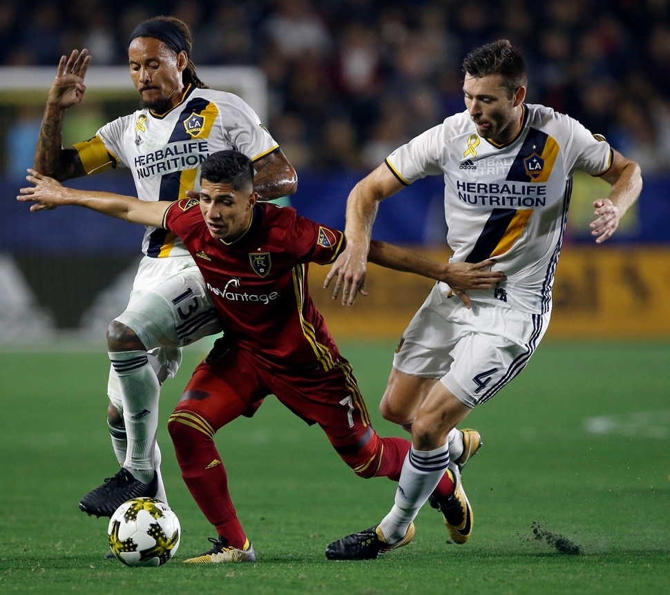 Real Salt Lake forward Jefferson Savarino, center, holds back Los Angeles Galaxy midfielder Jermaine Jones, left, and defender Dave Romney from the ball during the second half of an MLS soccer game in Carson, Calif., Saturday, Sept. 30, 2017. (AP Photo/Alex Gallardo)