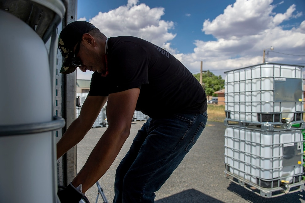 (Leah Hogsten | The Salt Lake Tribune) Donovan Smallcanyon, a solar and water technician on the Navajo Water Project for DigDeep, manuvers a 250-gallon water tank in Dilkon, Ariz., June 23, 2020. Smallcanyon keeps solar-powered panel systems and propane hot water heaters working and fills cisterns at least once a month for residents in Navajo Mountain and Piute Mesa in San Juan County.
