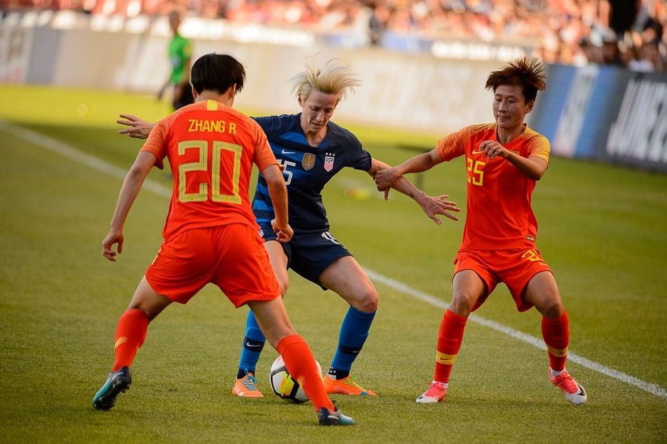 (Trent Nelson | The Salt Lake Tribune) USA forward Megan Rapinoe is defended by China PR midfielder Zhang Rui and China PR forward Lou Jiahui during the international friendly match between China and the USA at Rio Tinto Stadium in Sandy, Utah, Thursday June 7, 2018.