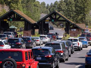 (John Burcham|The New York Times) Cars line up at the South Rim entrance of Grand Canyon National Park in Arizona on July 2, 2021. Americans are flocking to national parks in record numbers, in many cases leading to long lines and overcrowded facilities. Here's what four parks looked like over the holiday weekend.