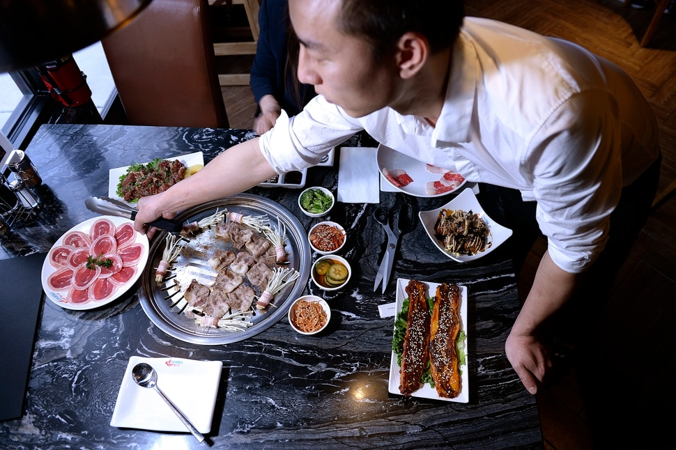 (Scott Sommerdorf | The Salt Lake Tribune) Chef Hiailiang Nee arranges dishes on the table at Ombu Grill, an all-you-can eat Korean barbecue restaurant, where customers cook thinly sliced meats and vegetables at their table.