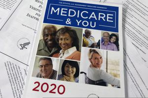 (Wayne Partlow | AP photo)  In this Feb. 13, 2020, photo, The Official U.S. Government Medicare Handbook for 2020 over pages of a Department of Health and Human Services, Office of the Inspector General report, are shown in Washington.