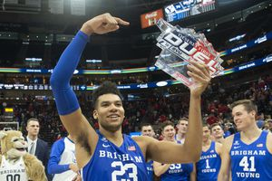 (Rick Egan     The Salt Lake Tribune)   Brigham Young forward Yoeli Childs (23) celebrates with the Deseret First Duel Trophy in basketball action in the Beehive Classic, between against the Brigham Young Cougars and Utah Utes, a the Vivint Smart Home Arena, Saturday December 8, 2018.