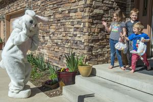 (Rick Egan  |  The Salt Lake Tribune)     Harper, Porter, and Everette Johnson wave at the Easter Bunny, from their front porch in Draper. Draper City Parks and Recreation workers along with the police and the fire department, delivered more than 30,000 Easter eggs to children at their doorsteps, Friday, April 10.