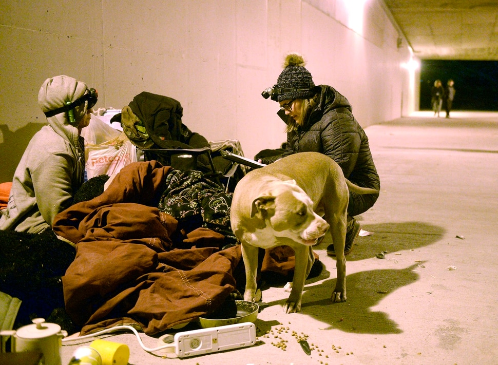 (Al Hartmann | The Salt Lake Tribune) Charly Swett, with Volunteers of America, right, interviews Thumper for the annual Point In Time count of homeless people in Salt Lake City at 4:30 a.m. Thursday, Jan. 25, 2018. Thumper has been homeless off and on for 25 years, and spent the night with a couple friends camped in the tunnel between Sugar House Park and Hidden Hollow. Hank a friend's dog in foreground.