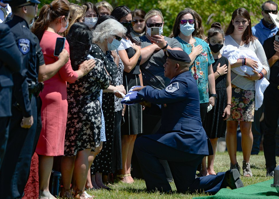 (Francisco Kjolseth | The Salt Lake Tribune ) Master Sgt. Christopher Stevens of the Utah Air National Guard presents his mother, Sharon, with his father's flag that covered the casket holding Dallas Lynn Stevens at the Utah Veterans Cemetery in Bluffdale on Wednesday, June 24, 2020.