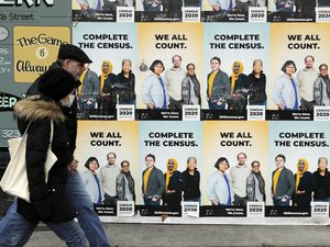 (AP Photo/Ted S. Warren, File) In this April 1, 2020, file photo, people walk past posters encouraging participation in the 2020 Census in Seattle's Capitol Hill neighborhood. The Church of Jesus Christ of Latter-day Saints is encouraging its members to fill out their census forms.