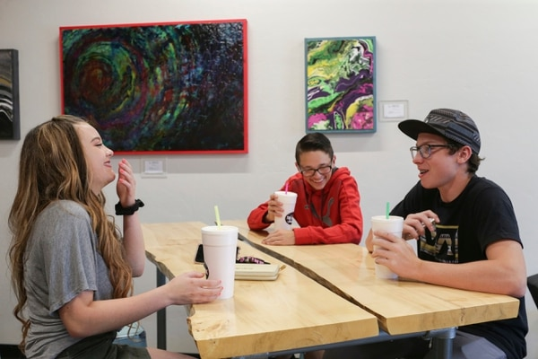 (John Roark/The Idaho Post-Register via AP) In a June 7, 2018, photo, Laurna Chapman, Landon Pinnock, with hat, and JR Chapman have sodas at The Drink Factory in Idaho Falls, Idaho. Soda shops, also known as soda shacks, have become a mainstay in the region.