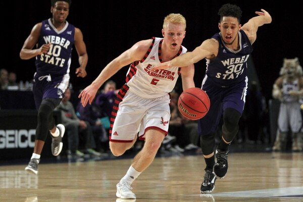 Eastern Washington guard Ty Gibson (2) chases down a loose ball in front of Weber State guard Jememy Senglin (30) during the first half an NCAA college basketball game in the semifinals of the Big Sky tournament in Reno, Nev., Friday, March 10, 2017. (AP Photo/Lance Iversen)