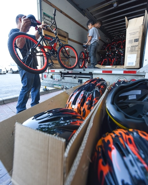 (Francisco Kjolseth | The Salt Lake Tribune) Volunteers and workers at Squatter's Pub Brewery assemble 80 bicycles on Tuesday, May 29, 2018, at the brewery which will be given away to 1st and 2nd graders at Washington Elementary on Wednesday as they are loaded onto a truck. Part of the program is backed by the Can'd Aid Foundation.