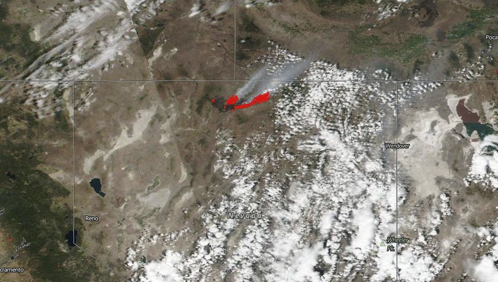 FILE - This July 8, 2018, satellite file image from NASA's Suomi NPP satellite shows a wildfire, shown in red, also known as the Martin Fire, in Nevada, and smoke reaching to Idaho. Destruction of sage grouse habitat by a series of large wildfires has prompted a ban on hunting for the game bird this fall across a stretch of north-central Nevada nearly twice as big as the state of Delaware. The Nevada Board of Wildlife Commissioners approved the emergency closure Friday, Aug. 17, 2018, of two specific hunting units in Humboldt and Elko counties. The Nevada Department of Wildlife says at least 39 known breeding sites supporting about 750 male sage grouse were destroyed in July by the Martin Fire. (NASA via AP, File)