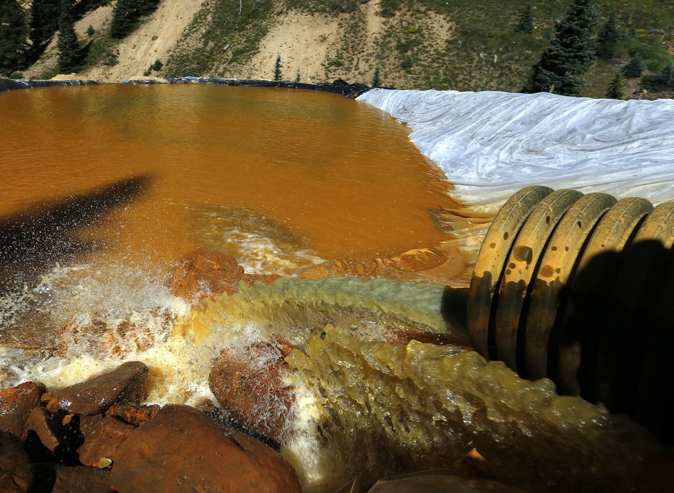 FILE - In this Aug. 14, 2015, file photo, water flows through a series of sediment retention ponds built to reduce heavy metal and chemical contaminants from the Gold King Mine outside Silverton, Colo. The U.S. government settled a lawsuit Wednesday, Aug. 5, 2020, brought by the state of Utah over a mine waste spill caused by federal workers that sent wastewater downstream to several states from the inactive Gold King Mine in southwestern Colorado five years ago. (AP Photo/Brennan Linsley, File)