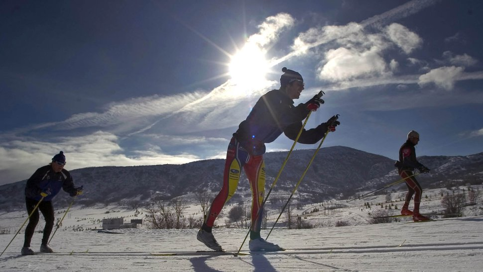 (Al Hartman | Tribune file photo) Cross-country skiers glide by and take in the clear sky and bright sun at Soldier Hollow Nordic Center, outside Midway, Utah.
