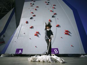 (Eugene Hoshiko   AP) A Tokyo 2020 Olympic Games Organizing staff mops the floor in front of the climbing wall in the test event of Speed Climbing in preparation for the Tokyo 2020 Olympic Games at Aomi Urban Sports Park in Tokyo, March 6, 2020. The tentacles of canceling the Tokyo Olympics — or postponing or staging it in empty venues — would reach into every corner of the globe, much like the spreading virus that now imperils the opening ceremony on July 24.