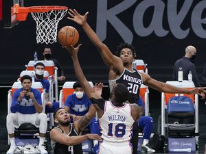 Philadelphia 76ers guard Shake Milton, center, goes to the basket against Sacramento Kings' Cory Joseph, left, an Hassan Whiteside, right,during the first half of an NBA basketball game in Sacramento, Calif., Tuesday, Feb. 9, 2021. (AP Photo/Rich Pedroncelli)