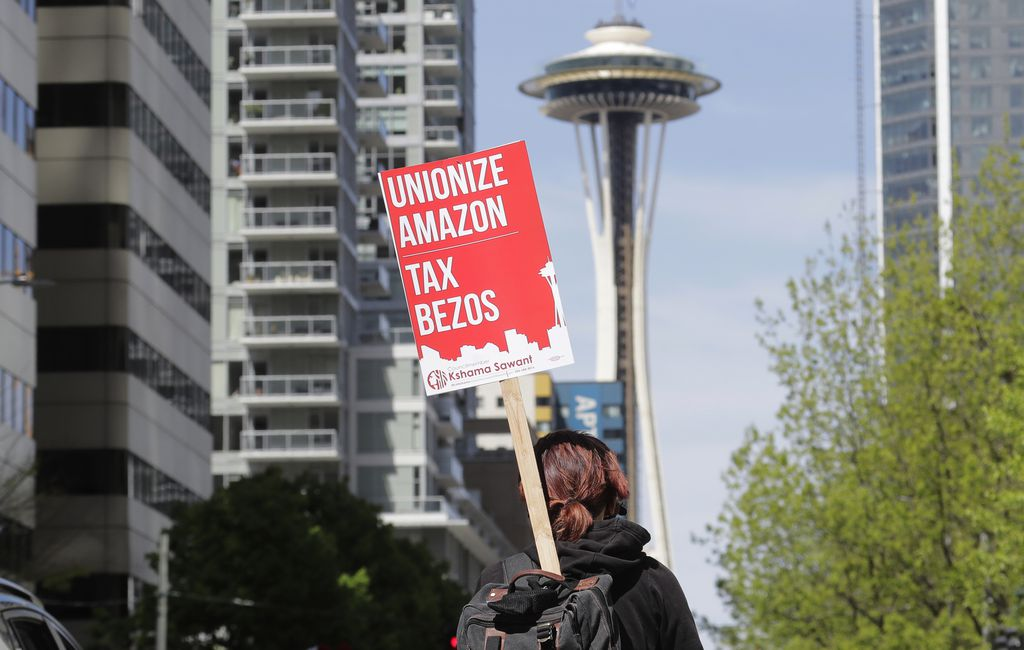 """FILE - In this May 1, 2020, file photo, a protester carries a sign that reads """"Unionize Amazon Tax Bezos,"""" in reference to Amazon founder and CEO Jeff Bezos, while riding a bike during a car-based protest at the Amazon Spheres in downtown Seattle. Mary's Place, a family homeless shelter located nearby inside an Amazon corporate building on the tech giant's Seattle campus, marks a major civic contribution bestowed by Amazon to the hometown it has rapidly transformed. But the Mary's Place family homeless shelter also serves as a stark display of have-and-have-nots, given that some blame the tech giant's explosive growth over the past decade for making living in Seattle too costly for a growing number of people. (AP Photo/Ted S. Warren)"""