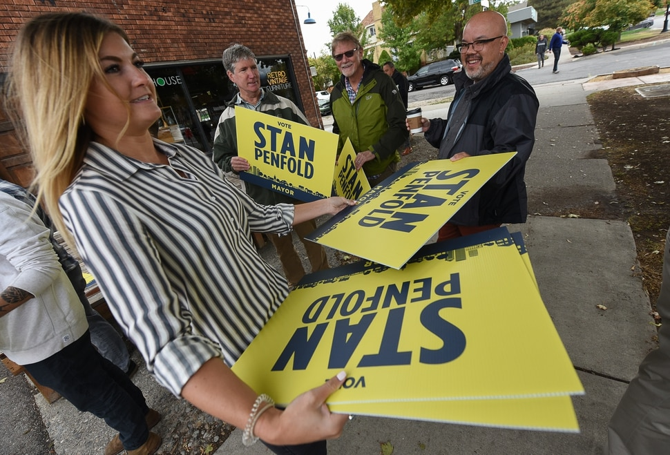 (Francisco Kjolseth | The Salt Lake Tribune) Emily Young hands out signs to supporters as former Salt Lake City Councilman Stan Penfold gets ready to announce his bid for mayor in the 9th East and 9th South area of Salt Lake City on Thursday, Oct. 4, 2018.