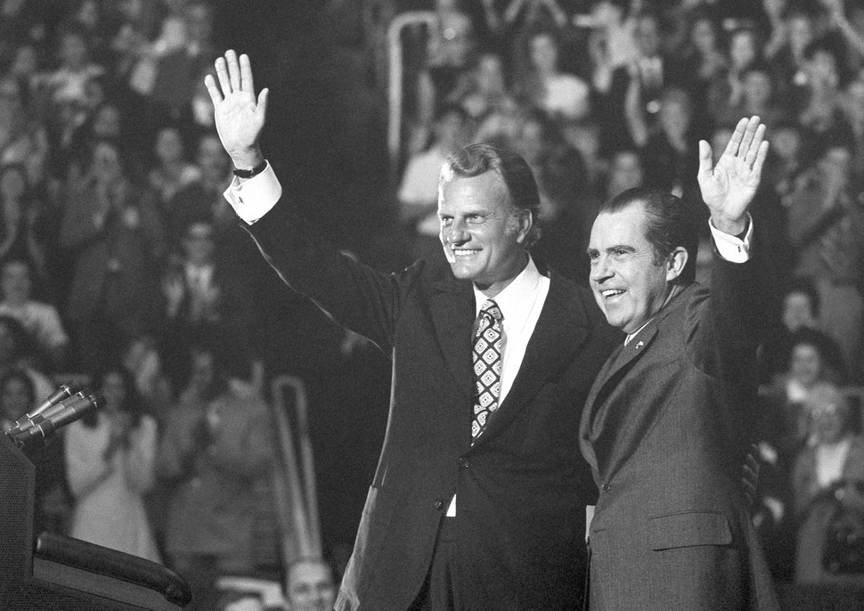 (AP Photo, File) In this Oct. 16, 1971, photo, evangelist Billy Graham and President Richard Nixon wave to a crowd of 12,500 at ceremonies honoring Graham at Charlotte, N.C.