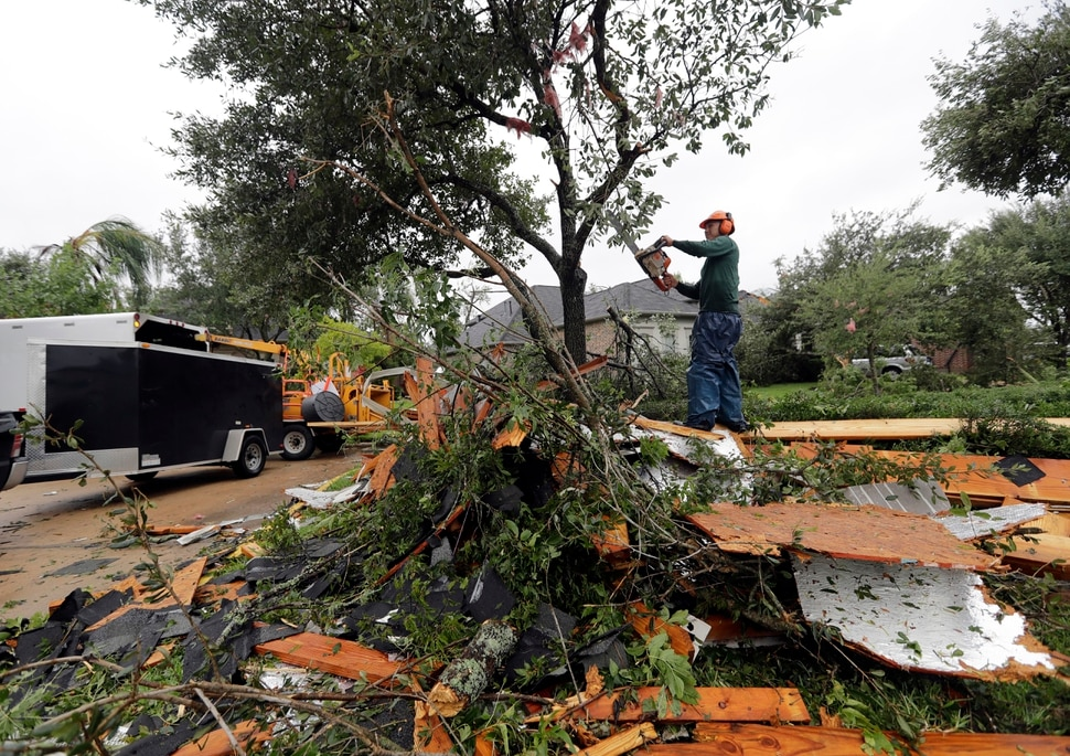 (David J. Phillip | The Associated Press) Henry Isaac cuts down broken tree limbs after Hurricane Harvey Saturday, Aug. 26, 2017, in Missouri City, Texas. Harvey rolled over the Texas Gulf Coast on Saturday, smashing homes and businesses and lashing the shore with wind and rain so intense that drivers were forced off the road because they could not see in front of them.