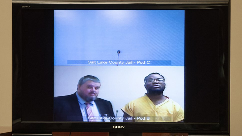 (Steve Griffin/Deseret News, via AP Photo, Pool) Attorney Neal Hamilton, left, stands with Ayoola A. Ajayi during his video preliminary hearing at the Matheson Courthouse Monday, July 15, 2019, in Salt Lake City. Ajayi, a tech worker charged in the death of a Utah college student, appeared by video from jail alongside a court-appointed attorney during a quick hearing to set a future court date. He did not speak or enter a plea to murder, kidnapping and other charges.