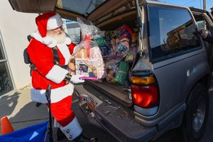(Francisco Kjolseth  |  The Salt Lake Tribune)  Santa, played by Merlin Taylor, pitches in as he joins a team of volunteers with the Granite Education Foundation's Santa Sacks program at a workshop in South Salt Lake on Tuesday, Dec. 3, 2019. In its 10th year, the program works with social workers throughout 60 schools in the district to help low income families struggling through the holidays as Santa helped fill a social workers car bound for two schools in the district.