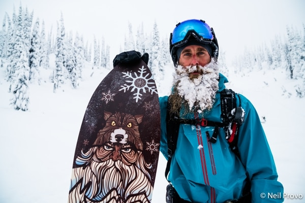 "(Courtesy Warren Miller Entertainment) Bushy-bearded Ian Provo of Oakley poses proudly with his powdersurfing board while visiting Mustang Lodge in British Columbia along with his brother, Neal, Scotty Arnold of Park City and Jeremy Jensen of Logan in Warren Miller's latest ski film, ""Line of Descent,"" whose national tour begins Friday at Abravanel Hall in Salt Lake City."