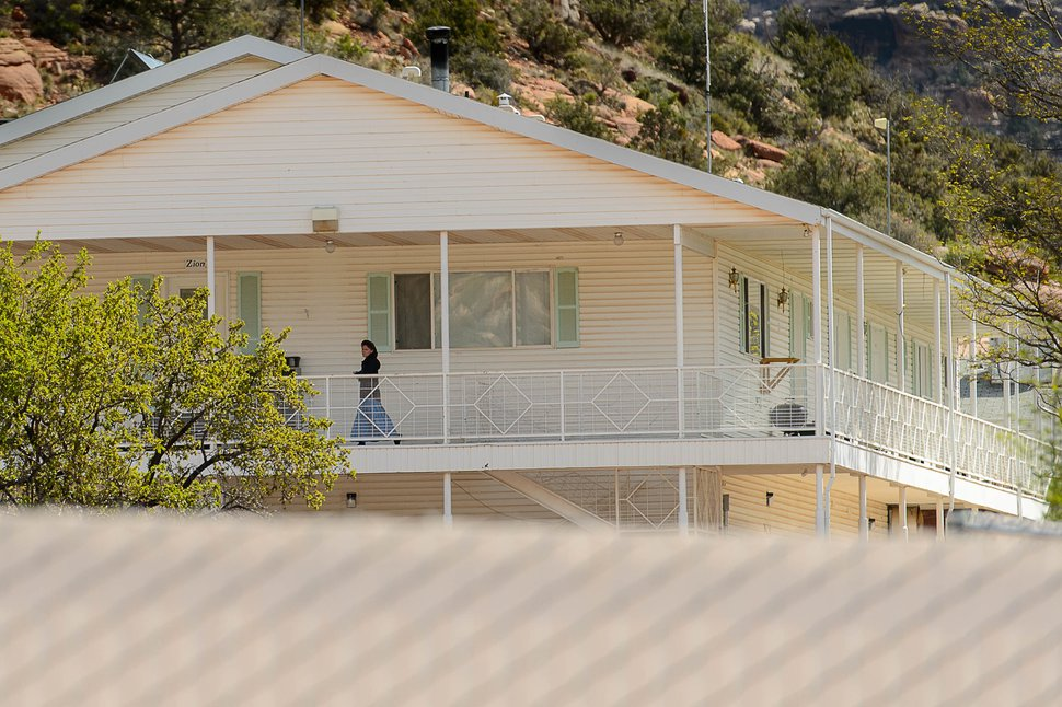 Trent Nelson | The Salt Lake Tribune A woman walks along the balcony of a large home that once housed FLDS Bishop Fred Jessop in Hildale, Thursday April 6, 2017. Perhaps more than 100 people are currently living in the home and facing eviction from the UEP Trust property.
