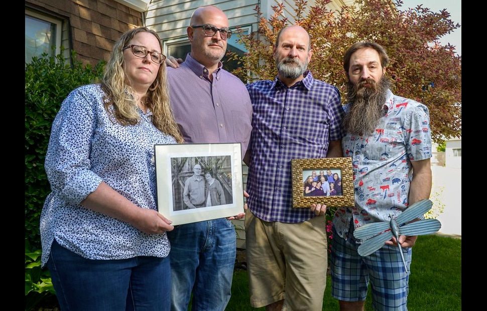 (Leah Hogsten | The Salt Lake Tribune) Six people in the Moody family contracted COVID-19. Siblings Rick Moody, center left, and Robert Moody, center right and their respective spouses, Laura and Glen Hoen, pose with photos of their parents and their family, May 28, 2020. Robert, Glen, Robert's father, John, mother, Carol Ann, and brother Roger and sister-in-law Hilary Moody all had the virus. Carol Ann Moody died from COVID-19.