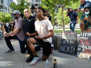 (Francisco Kjolseth     The Salt Lake Tribune) Salt Lake City Police Chief Mike Brown, center, takes a knee as he is joined by Robert Jenkins, left, and Aristide Gateretse, showing support of demonstrators protesting against police brutality on Wednesday, June 3, 2020, in downtown Salt Lake City.