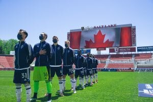 (Vancouver Whitecaps/Laura Dearden) Members of the Vancouver Whitecaps stand and listen during the Canadian national anthem. The Whitecaps are currently living in the Salt Lake City area due to travel restrictions brought on by the COVID-19 pandemic and using Real Salt Lake's facilities.