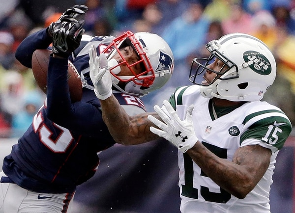 New England Patriots defensive back Eric Rowe, left, intercepts a pass intended for New York Jets wide receiver Brandon Marshall (15) during the first half of an NFL football game, Saturday, Dec. 24, 2016, in Foxborough, Mass. (AP Photo/Elise Amendola)