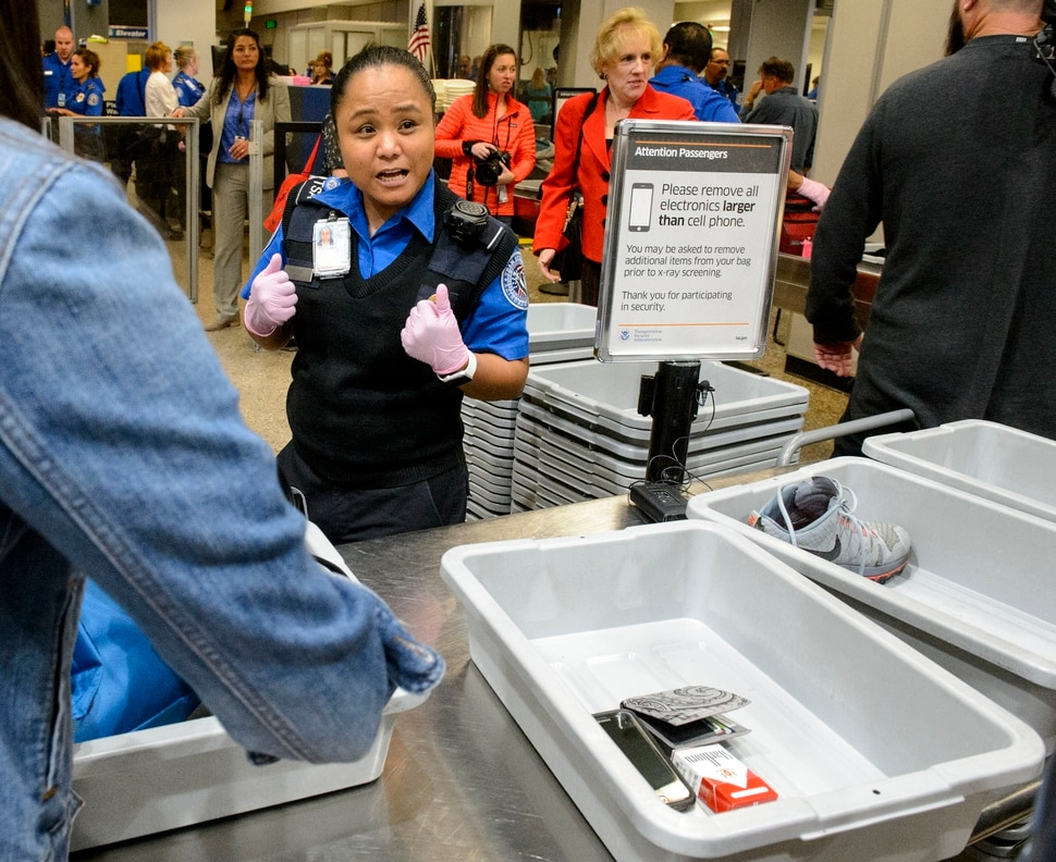 (Steve Griffin | The Salt Lake Tribune) TSA agent Joyce Domingo helps airline passengers as they go through security at Salt Lake International Airport Thursday October 5, 2017. TSA has implemented stronger carry-on baggage screening for electronic devices where any electronic device larger than a cell phone needs to be in bins for X-ray.