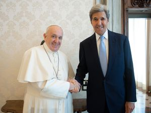 """(Vatican Media via AP) Pope Francis and John Kerry, right, shake hands as they pose for a photo at the Vatican, Saturday, May 15, 2021. Former U.S. Secretary of State John Kerry, currently President Biden's envoy on the climate, met in private audience with Pope Francis on Saturday, afterward calling the pope """"a compelling moral authority on the subject of the climate crisis"""" who has been """"ahead of the curve."""" Kerry told Vatican News in an interview that the pope speaks with """"unique authority, compelling moral authority, that hopefull can push people to greater ambition to get the job done."""