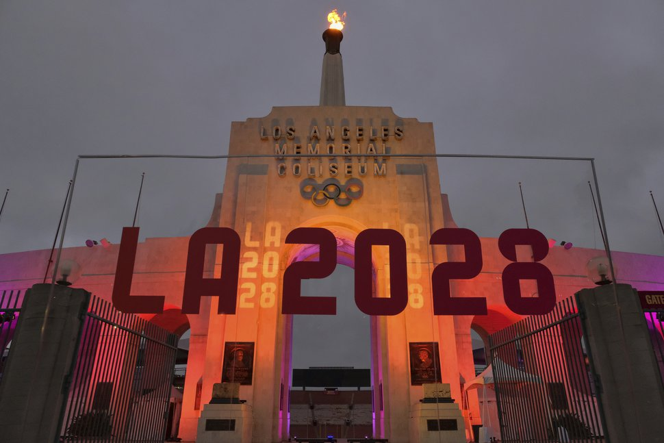 (AP Photo/Richard Vogel, File)In this Sept. 13, 2017, file photo, an LA 2028 sign is seen in front of a blazing Olympic cauldron at the Los Angeles Memorial Coliseum.