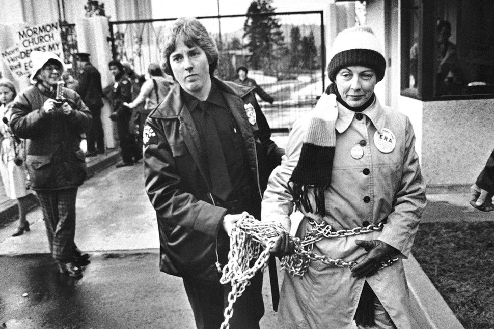 (AP file photo) Sonia Johnson is led away from a Latter-day Saint temple by a police officer after she had chained herself to the gate during a pro-Equal Rights Amendment demonstration in Bellevue, Wash., on Nov. 17, 1980.