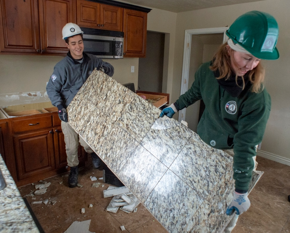 (Rick Egan | The Salt Lake Tribune) Uri Sarig and Meghan Schwob with AmeriCorps, remove a kitchen counter for UDOT and Habitat for Humanity from a home that will be demolished for freeway widening, for use in Habitat for Humanity homes, Wednesday, Jan. 16, 2019.