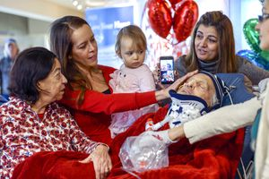 (Leah Hogsten  |  The Salt Lake Tribune)  l-r Lucia Silva, daughter Flavia Beare, granddaugher Petra Beare, and family friend Cristina Tesolin caress the face of their husband and father, Osvaldo Silva. On Friday, Intermountain Hospital caregivers wheeled paralyzed cancer patient Osvaldo Silva, 85, down to the lobby for a personal piano concert in his honor, Feb. 15, 2019. With tears streaming down his face, Osvaldo, who is from Brazil, was treated to a dozen songs played by his Church of Jesus Christ of Latter-day Saints bishop, Bispo Do Pai Valdir, who kicked off the set with none other than ÒThe Girl from Ipanema.Ó