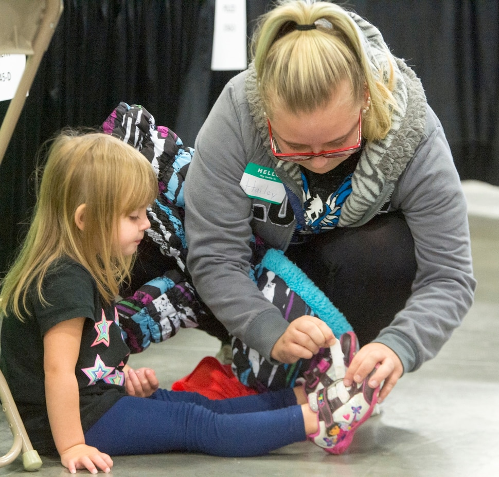 (Rick Egan | The Salt Lake Tribune) Hailey Bartlett fastens the shoes for her 3-year-old daughter, Abigail Fletcher, during Project Homeless Connect on Friday, Oct. 6, 2017. The one-day event in Salt Lake City brings together community volunteers to provide services for individuals and families experiencing homelessness.