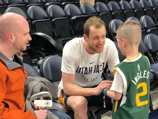 Joe Ingles chats pregame with Landon Carter, an 8-year-old fan. Ingles gifted Carter, who is legally blind, a $10,000 pair of goggles from eSight that allows him to see high-definition images of the world around him. Along with his father, Jeff Carter, Landon watched the game in the crowd at Vivint Smart Home Arena on March 15, 2018. Photo by Angela Treasure. Courtesy of the Utah Jazz.