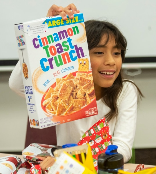 (Rick Egan | The Salt Lake Tribune) Laylani Eontalez, 3rd grade, shows her classmates the box of cereal she opened. Ms. Worthington the principal, surprised all 650 students at her school with the gift-wrapped boxes of cereal, at Oquirrh Elementary in West Jordan, Thursday, Dec. 20, 2018.