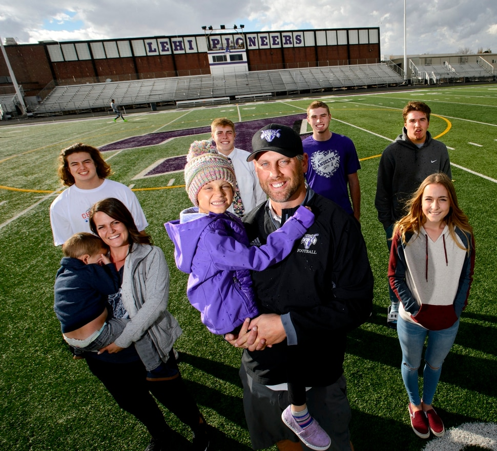 (Steve Griffin | The Salt Lake Tribune) Lehi assistant football coach Andy Hadfield and his wife Jessica with their children Cohen, age 2, Andelyn, age 5, and Kadence, age 12, are joined by Lehi football players Lincoln Bunker, Landan McAllister, Kyler Welsh and Dallin Holker on the school's football field in Lehi, Utah Sunday November 5, 2017. Andelyn is battling cancer and the football team has rallied around her.