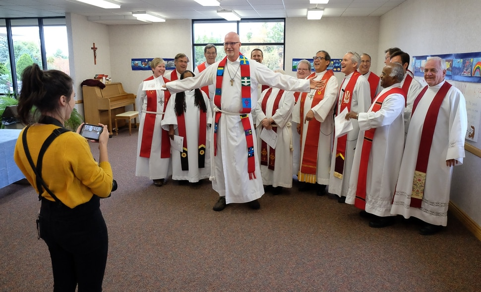 (Francisco Kjolseth | The Salt Lake Tribune) Rev. David Nichols tries to steal the spotlight for a group photo as Lutheran and Catholic priests gather at Zion Evangelical Lutheran Church in Salt Lake City for an ecumenical prayer service.