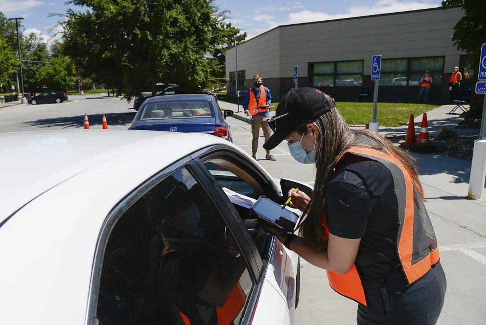(Francisco Kjolseth | Tribune file photo) Poll worker Kellie Madsen helps a voter lined up at one of twelve drive-up voting assistance centers in Salt Lake County, Utah, at the Northwest Recreation Center on June 30, 2020.,