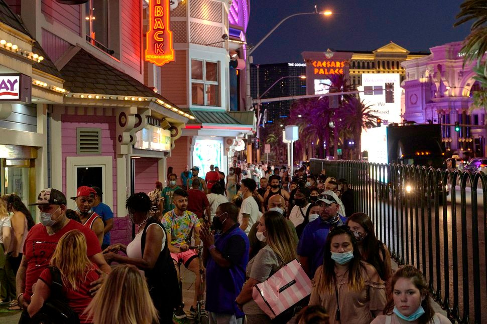 (Bridget Bennett | The New York Times) People walk along the Strip in Las Vegas, July 31, 2020. Remote U.S. destinations, where social distancing is easier, are generally faring better than cities, which are trying hard to get a bigger share of the leisure crowd.