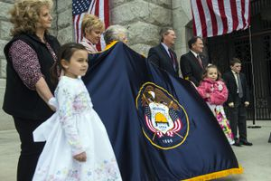 (Chris Detrick  |  Salt Lake Tribune file photo) Children hold an embroidered Utah state flag at a 2014 ceremony to mark the 100th anniversary of the laying of the Utah State Capitol's cornerstone. Then-Gov. Gary Herbert and one of his predecessors, Mike Leavitt, are seen attending the ceremony.