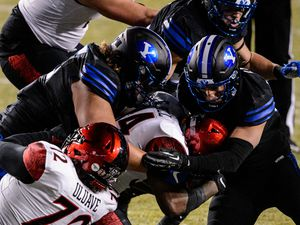(Trent Nelson  |  The Salt Lake Tribune) Brigham Young Cougars defensive lineman Khyiris Tonga (95) and Brigham Young Cougars linebacker Isaiah Kaufusi (53) tackle San Diego State Aztecs running back Greg Bell (34) as BYU hosts San Diego State, NCAA football in Provo on Saturday, December 12, 2020.