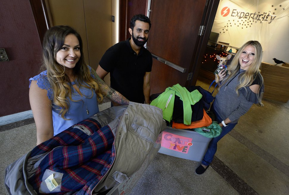 (Scott Sommerdorf | The Salt Lake Tribune) Experticity staff Jesse Craner, left, Rico Alderete and Anna Farnsworth, right, hold jackets they will donate to The Road Home during a drive to collect coats for the homeless, Wednesday, October 25, 2017. The effort is one of the team building activities used by the marketing/branding company to involve their employees in helping the community - an opportunity that workers say motivates them to do better all around.